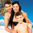 Happy family with child at tropical beach — Stock Photo