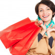 Happy woman with shopping bags in beige autumn coat - Stockfoto