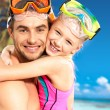 Happy smiling father hugs daughter at tropical beach - Stock Photo