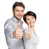 Portrait of happy couple with thumbs up sign — Stock Photo