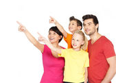Family with two children pointing finger up — Stock Photo