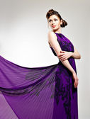 Beautiful fashion woman in violet long dress — Stock Photo