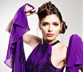 Mode vrouw in violet jurk met stijlvolle kapsel — Stockfoto