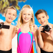 Children with photo and video camera at beach. — Stock Photo
