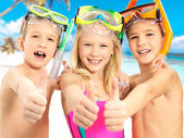 Happy children with thumbs-up gesture at beach — Stock Photo