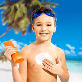 Boy applying sun block cream on the tanned body — Stock Photo