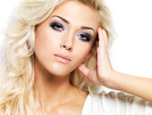 Beautiful blond woman with long curly hair and style makeup. — Stock Photo