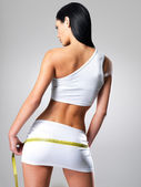 Sporty woman with slim body measuring hips — Stock Photo