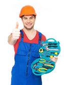 Handyman with tools showing thumbs up sign — Stock Photo