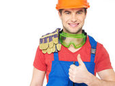Portrait of smiling worker shows thumbs up — Stock Photo