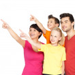 Family with two children pointing finger up - Stock Photo