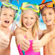Happy children with thumbs-up gesture at beach - Stockfoto