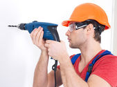 A man drilling a hole in the wall. — Stock Photo