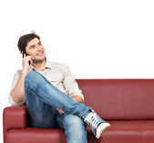Man sits on the divan and speaks on mobile phone — Stock Photo