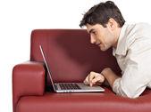 счастливый улыбающийся человек с ноутбуком на диване — Стоковое фото