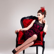 Woman with fashion hairstyle and red armchair — Stock Photo
