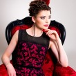 Woman with fashion hairstyle and red armchair — Stockfoto