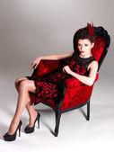 ファッション髪型と赤い肘掛け椅子と女性 — ストック写真