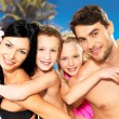 Happy family with two children at tropical beach - Stock Photo