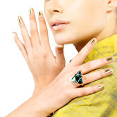 Women hands with golden nails and precious stone emerald — Stock Photo