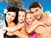 Happy family with two children at tropical beach — Stock Photo