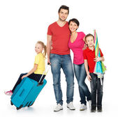 Happy family with suitcase at studio — Stock Photo