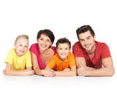 Happy family with two children lying on white floor — Stock Photo