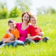 Young happy mother with children in park — Stock Photo #32077973