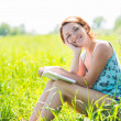 Pretty smiling woman reads the book at nature — Stock Photo