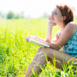 Pretty smiling woman reads the book at nature — Stock Photo #32078061