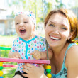 Happy mother with laughing baby sits on swing — Foto Stock