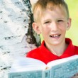 Schoolboy reading the book at  nature — Stock Photo