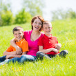 Young happy mother with children in park — Stock Photo