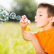 Young caucasian boy blowing the soap bubbles on nature — Stock Photo #32078123
