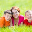 Young happy mother with children in park — Stock Photo #32078137