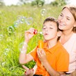 Mother and son in the park blowing soap bubbles  — Stock Photo