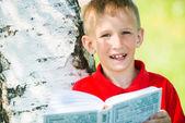 Schüler, die lektüre des buches auf die natur — Stockfoto