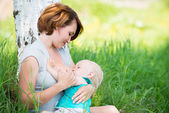 Young mother breastfeeding a baby in nature — Stock Photo