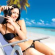 Woman with a camera taking photos on beach — Stock Photo #32812885