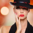 Beautiful woman with red lips and nails in black hat — Stock Photo #32813209
