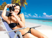 Woman with a camera taking photos on beach — Stock Photo
