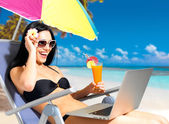 Happy woman on the beach with a laptop — Stock Photo