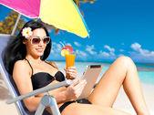 Happy woman on the beach with ipad — Stock Photo