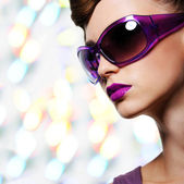 Beautiful woman in fashion violet sunglasses — Stock Photo