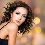 gezicht van mooie vrouw met lang krullend haren — Stockfoto