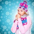 Beautiful woman in winter clothes warming her hands — Stock Photo #32890625