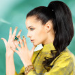 Woman with golden nails and emerald ring — Stock Photo