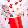 Woman with gifts after shopping to the new year at shop — Stock Photo #32890921