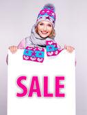 Frau im winter oberbekleidung hält die weiße fahne mit verkauf wort — Stockfoto