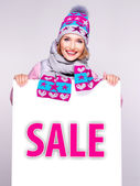 Woman in winter outerwear holds the white banner with sale word — Stock Photo